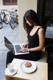 Ritratto di giovane lavoro della studentessa sul suo NET-libro mentre il testo di battitura a macchina durante il pranzo irrompe  Fotografia Stock