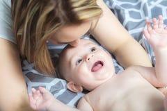 Ritratto di giovane madre felice con un bambino nel letto a casa fotografia stock libera da diritti