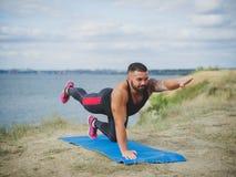 Ritratto di giovane maschio splendido, yoga di pratica all'aperto Addestramento esterno sotto il sole di mattina Immagine Stock