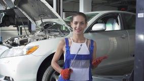 Ritratto di giovane meccanico femminile dello specialista con la chiave sui precedenti del meccanismo e dell'automobile di sollev archivi video