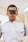 Ritratto di giovane medico con le lenti di ingrandimento binoculari dentarie sul suo fronte alla clinica del dentista Fotografie Stock Libere da Diritti