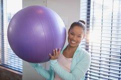 Ritratto di giovane medico femminile sorridente che tiene la palla porpora di esercizio Immagine Stock