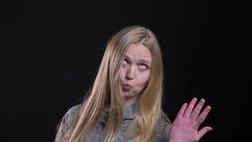 Ritratto di giovane modello diritto-dai capelli biondo che mostra le emozioni divertenti nella macchina fotografica su fondo nero video d archivio