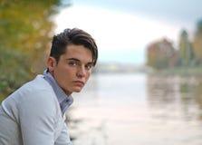 Ritratto di giovane modello maschio sul fiume fotografie stock