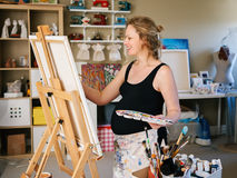 Ritratto di giovane pittura caucasica bianca sorridente del disegno della donna incinta che sta al cavalletto in studio domestico fotografia stock