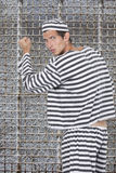 Ritratto di giovane prigioniero maschio in uniforme che sta contro la cella di prigione Fotografia Stock Libera da Diritti