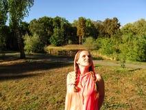 Ritratto di giovane ragazza adulta con un uso incappucciato, sorridere di due trecce, esaminante il cielo in parco Il concetto di fotografie stock
