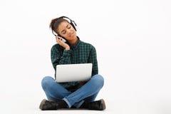 Ritratto di giovane ragazza africana con il computer portatile sopra fondo bianco Immagine Stock Libera da Diritti