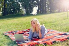 Ritratto di giovane ragazza attraente che lavora con il computer portatile in parco Fotografie Stock Libere da Diritti