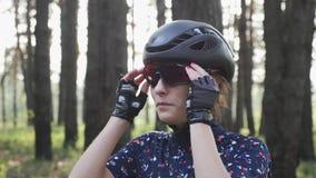 Ritratto di giovane ragazza attraente che mette i vetri sul casco nero d'uso prima di riciclaggio e sul jersey blu Concetto di ri archivi video