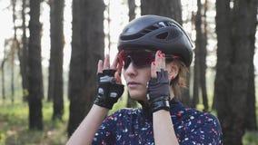 Ritratto di giovane ragazza attraente che mette i vetri sul casco nero d'uso prima di riciclaggio e sul jersey blu Concetto di ri video d archivio