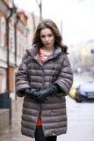 Ritratto di giovane ragazza castana alla moda in un piumino grigio Fotografie Stock Libere da Diritti