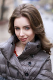 Ritratto di giovane ragazza castana alla moda in un piumino grigio Fotografia Stock