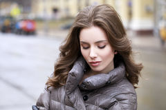 Ritratto di giovane ragazza castana alla moda in un piumino grigio Fotografie Stock