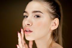 Ritratto di giovane ragazza castana con trucco naturale che tiene le sue dita sul suo fronte fotografie stock libere da diritti