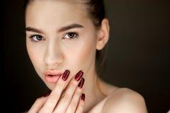 Ritratto di giovane ragazza castana con trucco naturale che tiene le sue dita sul suo fronte immagine stock libera da diritti