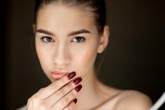 Ritratto di giovane ragazza castana con trucco naturale che tiene le sue dita sul suo fronte fotografia stock libera da diritti