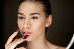 Ritratto di giovane ragazza castana con trucco naturale che tiene le sue dita sul suo fronte fotografia stock