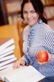 Ritratto di giovane ragazza castana sorridente felice dello studente con la mela fotografia stock libera da diritti