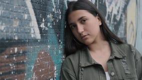 Ritratto di giovane ragazza castana triste dei pantaloni a vita bassa con gli occhi marroni vicino ad una parete con i graffiti stock footage