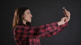 Ritratto di giovane ragazza dai capelli lunghi in camicia plaided che fa le belle selfie-foto facendo uso dello smartphone sul fo immagini stock
