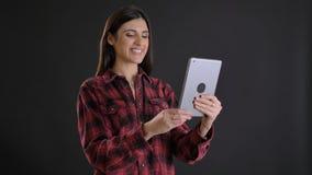 Ritratto di giovane ragazza dai capelli lunghi in camicia plaided che fa le selfie-foto felici facendo uso della compressa sul fo immagini stock libere da diritti