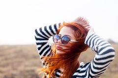 Ritratto di giovane ragazza della testarossa in occhiali da sole Fotografia Stock