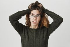 Ritratto di giovane ragazza europea con l'espressione pazza, sembrante maglione e vetri verdi stanchi e depressi, d'usi Fotografie Stock Libere da Diritti