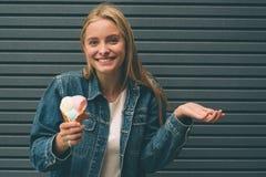 Ritratto di giovane ragazza felice che mangia gelato, all'aperto, sopra il fondo blu della parete immagini stock