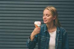 Ritratto di giovane ragazza felice che mangia gelato, all'aperto, sopra il fondo blu della parete fotografia stock libera da diritti
