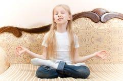 Ritratto di giovane ragazza graziosa con capelli biondi lunghi divertendosi seduta sul sofà che medita e che sbatte le palpebre e Immagini Stock