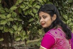 Ritratto di giovane ragazza indiana che riposa sotto un albero di banyan, portante il vestito tradizionale immagini stock libere da diritti