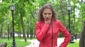 Ritratto di giovane ragazza preoccupata attraente in bomber rosso stock footage