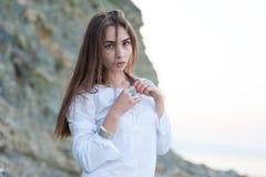 Ritratto di giovane ragazza sexy di hippy nello stile elegante di boho che posa contro il contesto delle rocce e del mare fotografie stock