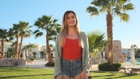 Ritratto di giovane ragazza sorridente dei pantaloni a vita bassa, esaminante macchina fotografica Bella donna in costume da bagn video d archivio