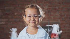 Ritratto di giovane ragazza sorridente del bambino dello scienziato in un laboratorio di chimica video d archivio