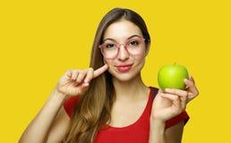 Ritratto di giovane ragazza sorridente del nerd della scuola che tiene una mela che gesturing come il buon alimento sano isolato  fotografia stock libera da diritti