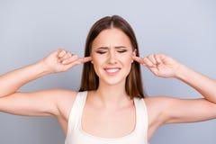 Ritratto di giovane ragazza sveglia stanca, chiudente le sue orecchie con le dita Immagine Stock Libera da Diritti