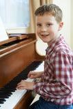 Ritratto di giovane ragazzo che gioca piano a casa Immagini Stock Libere da Diritti