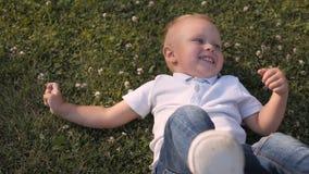 Ritratto di giovane ragazzo che si trova nell'erba Little Boy sveglio divertendosi all'aperto sul prato inglese stock footage