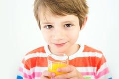 Ritratto di giovane ragazzo che sta bevendo il succo nei precedenti bianchi Immagine Stock