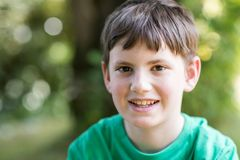 Ritratto di giovane ragazzo felice che si siede all'aperto fotografia stock