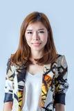 ritratto di giovane risata femminile attraente sulle sedere grigio chiaro Fotografie Stock