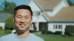 Ritratto di giovane riuscito uomo asiatico contro lo sfondo di nuova casa Concetto d'acquisto del bene immobile fotografia stock libera da diritti
