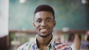 Ritratto di giovane riuscito uomo d'affari africano all'ufficio occupato Sorridere di sguardo maschio bello di inizio e della mac archivi video