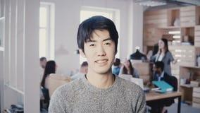 Ritratto di giovane riuscito uomo d'affari asiatico che sorride all'ufficio occupato Responsabile maschio bello che esamina macch video d archivio