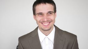 Ritratto di giovane riuscito uomo d'affari di risata attraente su un fondo bianco Movimento lento 3840x2160 video d archivio