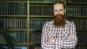 Ritratto di giovane sorridere barbuto dell'uomo felice in biblioteca e di esaminare macchina fotografica Fotografia Stock