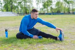 Ritratto di giovane sportivo che fa allungando esercizio, preparante per l'addestramento di mattina fotografie stock
