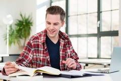Ritratto di giovane studente che sorride mentre ricercando informazioni Fotografie Stock Libere da Diritti